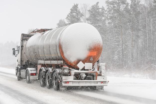 Cysterna paliwa na zimowej drodze. burza śnieżna.