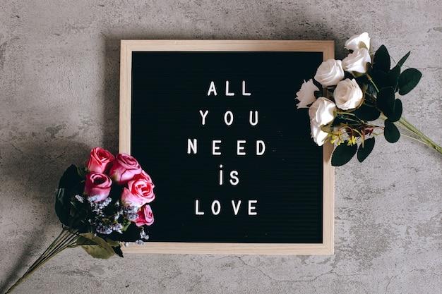 """Cytat na tablicy z listem mówi """"wszystko czego potrzebujesz to miłość"""" z kolorowym kwiatem róży"""
