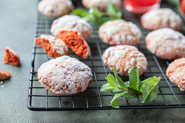 Cytrusowe chrupiące, pomarańczowe, marszczone ciasteczka z cukrem pudrem na czarnej metalowej kratce