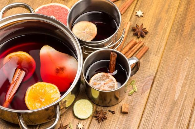 Cytrusowe grzane wino z przyprawami w metalowych kubkach i rondelku. anyż gwiazdkowy, kawałki pomarańczy i laski cynamonu na stole.
