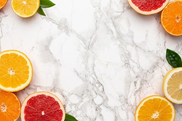 Cytrusy na marmurowej powierzchni z copyspace, płaska owocowa, minimalna letnia kompozycja z grejpfruta, cytryny, mandarynki i pomarańczy