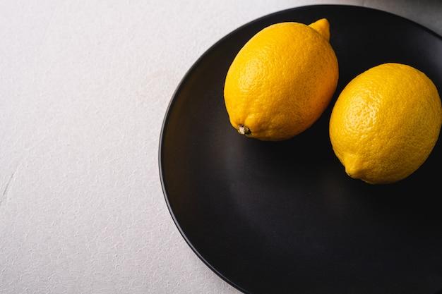 Cytryn kwaśne owoc w czarnym talerzu na bielu