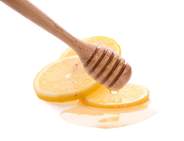 Cytryna i drewniana miodowa chochla odizolowywająca na biel ścianie