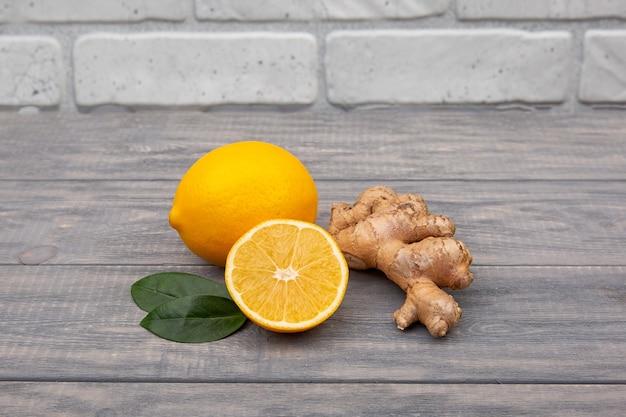 Cytryna i imbir na drewnianym tle. składniki przeciwko grypie i wirusom. składniki na herbatę. medycyna naturalna.