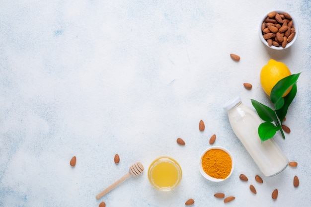 Cytryna, jogurt, orzech migdałowy, kurkuma i miód na białym tle. pięć produktów zapewniających odporność. menu żywności w tle.