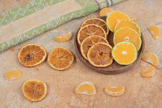 Cytryna, mandarynka i suszone plastry pomarańczy na drewnianym talerzu.