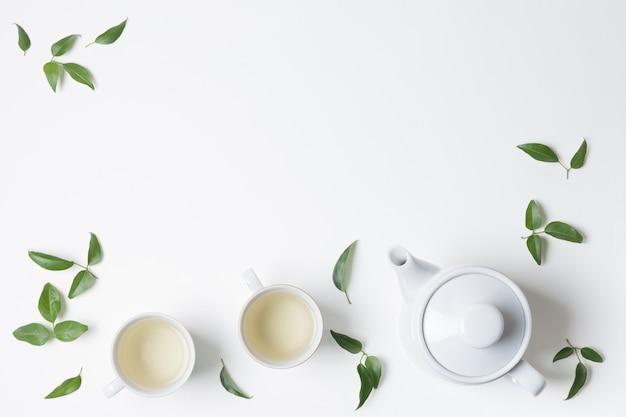 Cytryna opuszcza z filiżanką i teapot odizolowywającym na białym tle