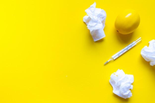 Cytryna, termometr i białe pigułki medyczne na żółtym tle, motyw apteki, leczenie i zapobieganie wirusom. pojęcie zdrowia w okresie przeziębienia.