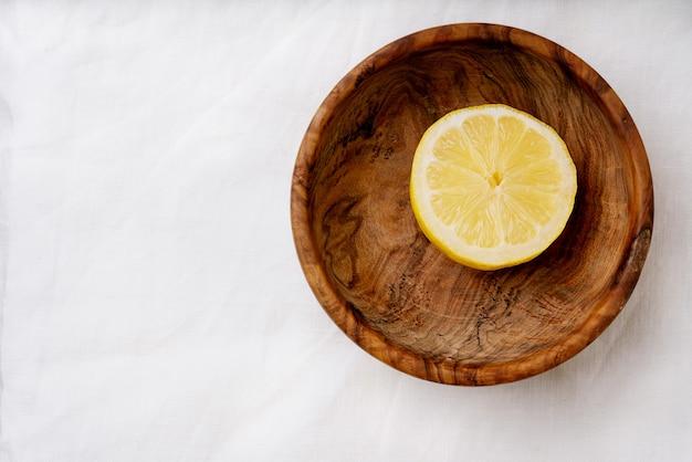 Cytryna w drewnianej misce. przekrojony na pół. widok z góry. flat lay. skopiuj miejsce