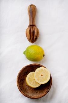 Cytryna w drewnianej misce z drewnianą wyciskarką. przekrojony na pół. biała powierzchnia tekstylna. widok z góry. flat lay. skopiuj miejsce