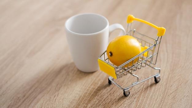 Cytryna w małym koszyku na kuchennym stole. w pobliżu znajduje się biały kubek herbaty. lekkie i nowoczesne zaplecze kuchenne.