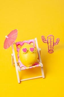 Cytryna w okularach przeciwsłonecznych w sunbed z umbrela przy plażą