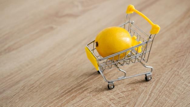 Cytryna w wózku supermarketu na stole w kuchni - drewniane tła. koncepcja zakupów online. koncepcja małego budżetu
