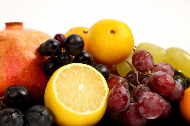 Cytryna, winogrona i granat na białej powierzchni