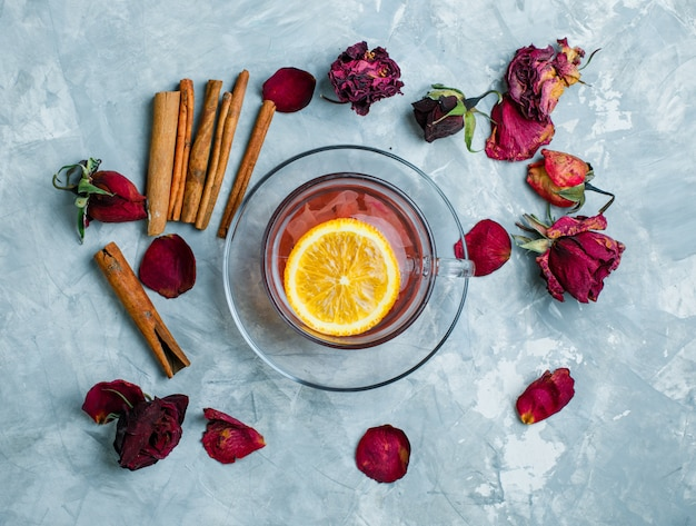 Cytrynowa herbata z cynamonowymi kijami, wysuszone róże w filiżance na grungy błękitnym tle, odgórny widok.