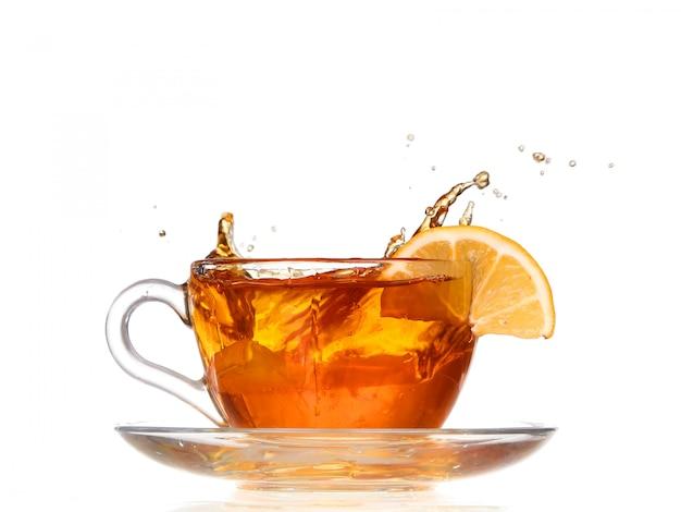 Cytrynowa herbata z pluśnięciem na białym tle