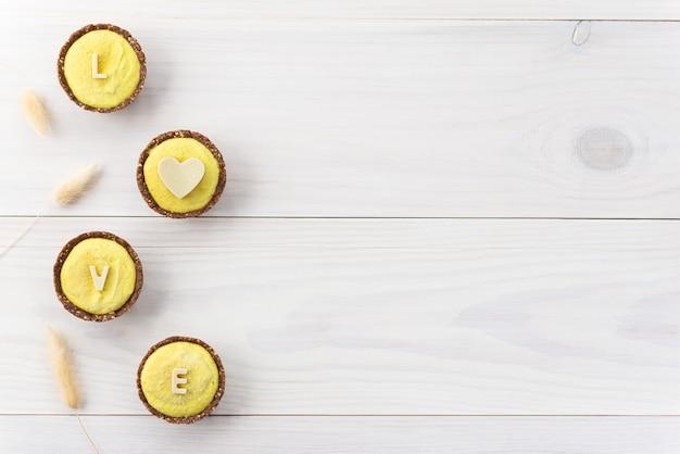 """Cytrynowe ciastka z nerkowca z napisem """"love"""" wykonane z białej czekolady na drewnianym stole."""