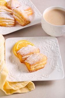 Cytrynowe madeleines z cukrem pudrem, podawane z kawą