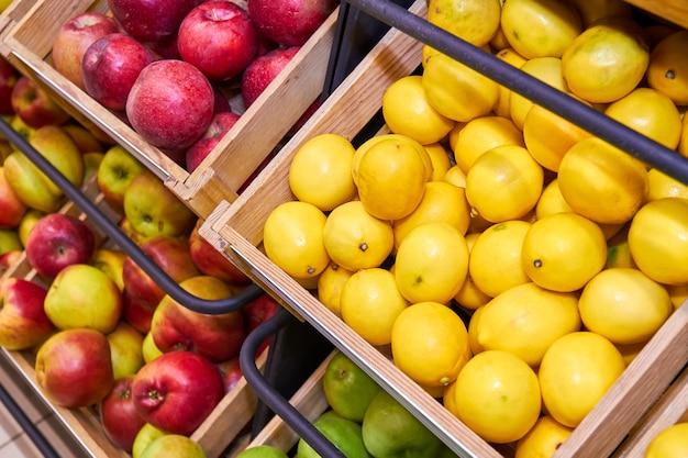 Cytryny, czerwone i zielone jabłka w drewnianych pudełkach na sklepowych półkach