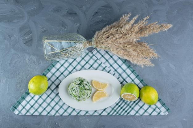 Cytryny, gotowany ryż i ozdobne łodygi na złożonym obrusie na marmurowym stole.