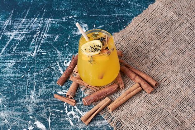 Cytryny i cynamony przy filiżance napoju na niebiesko.