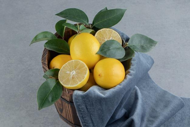 Cytryny i liście ułożone w wiadrze na marmurze
