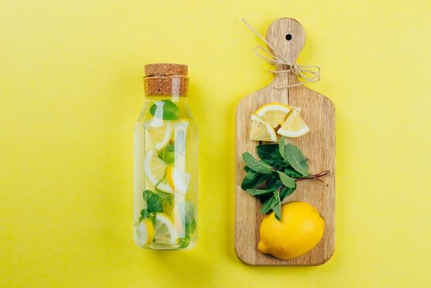 Cytryny lemoniada w szklanej butelce i składnikach na drewnianych tnących deskach na żółtym tle