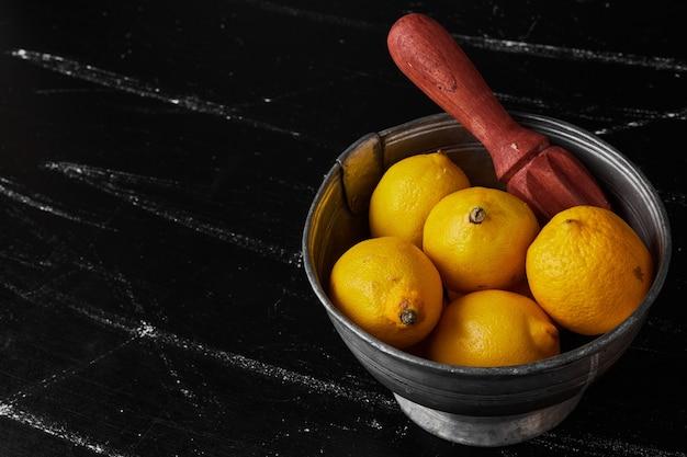 Cytryny na białym tle w metalowej filiżance.