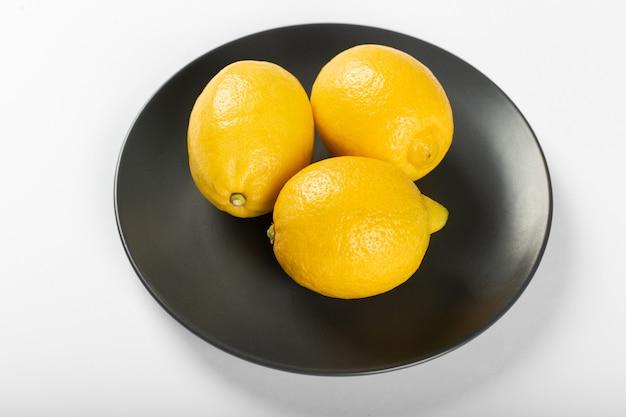 Cytryny na czarnym ciemnym spodku