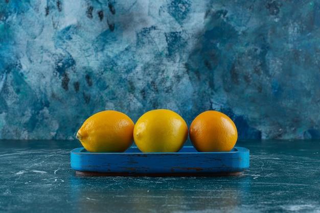 Cytryny na drewnianym talerzu, na marmurowym stole.