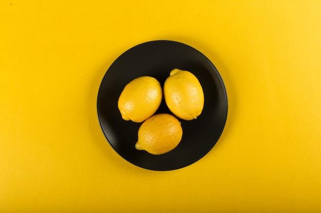 Cytryny na talerzu na kolorze żółtym