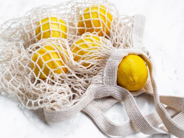 Cytryny pod dużym kątem w bawełnianej torbie z siatki
