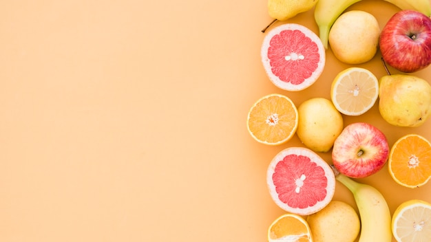 Cytryny przekrojowe; pomarańczowy; jabłko; gruszki i banan na beżowym tle