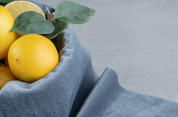 Cytryny w wiadrze pokrytym kawałkiem tkaniny na marmurze