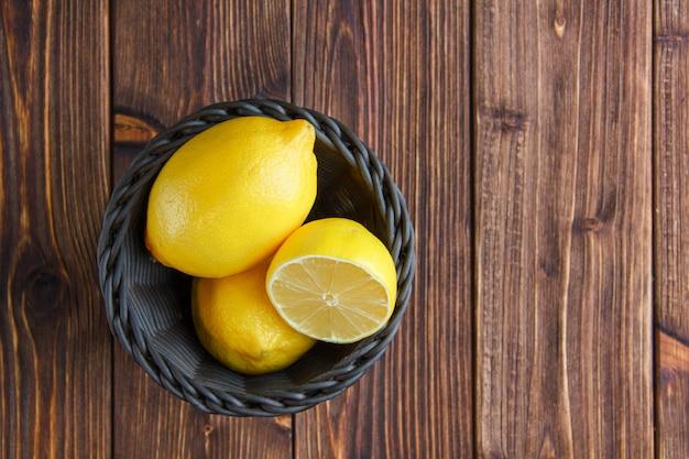 Cytryny w wiklinowym koszu na drewnianym stole. leżał płasko.