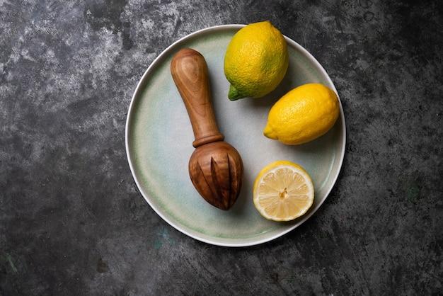 Cytryny z drewnianą wyciskarką na niebieskim talerzu ceramicznym. flat lay. widok z góry. skopiuj miejsce
