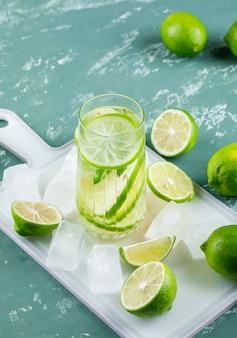 Cytryny z kostkami lodu, lemoniady wysoki kąt widzenia na gipsie i deska do krojenia