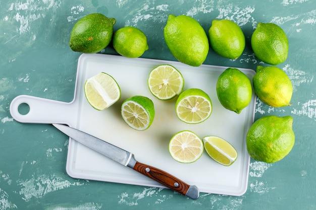 Cytryny z plastrami, nóż na gipsie i deska do krojenia,