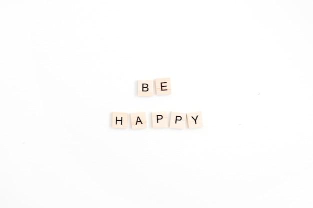 Cytuj bądź szczęśliwy z drewnianymi kafelkami na białym tle