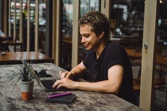 Człowiek pracuje z laptopem w kawiarni na drewnianym stole