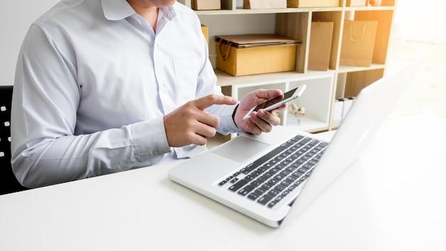 Cz? owiek posiadania karty kredytowej w parze i wprowadzania kodu zabezpieczaj? cego przy u? yciu inteligentnego telefonu na klawiaturze laptopa, koncepcji zakupów online
