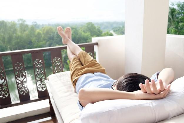 Cz? owiek relaks w fotelu i korzystaj? z widoku z tarasu.