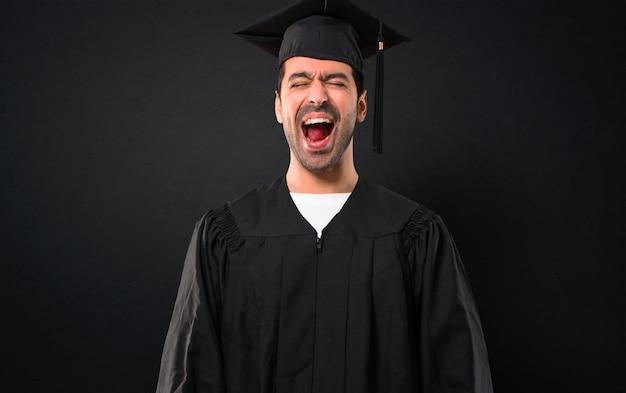 Cz? owiek w dniu jego ukończenia uniwersytet krzyczy do przodu z usta szeroko otwarte na czarnym tle