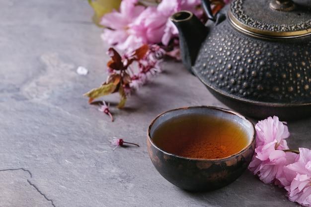 Czajniczek i filiżanka herbaty z gałąź kwiat