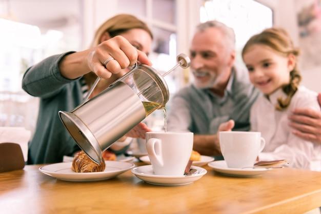Czajniczek. kobieta trzyma mały dzbanek do herbaty z zieloną herbatą, wlewając go do filiżanki o śniadanie w kawiarni
