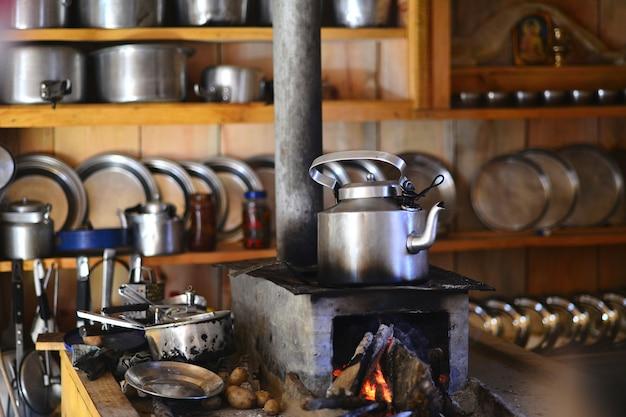 Czajniczek w wysokogórskiej kuchni z ogniem i naczyniami w nepalu.