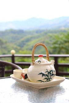 Czajniczek z filiżankami herbaty ze świeżym naturalnym tłem koncepcja relaksu i odpoczynku