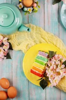 Czajniczek z kawałkiem kolorowego ciasta i brązowymi jajkami na przyjęcie wielkanocne.