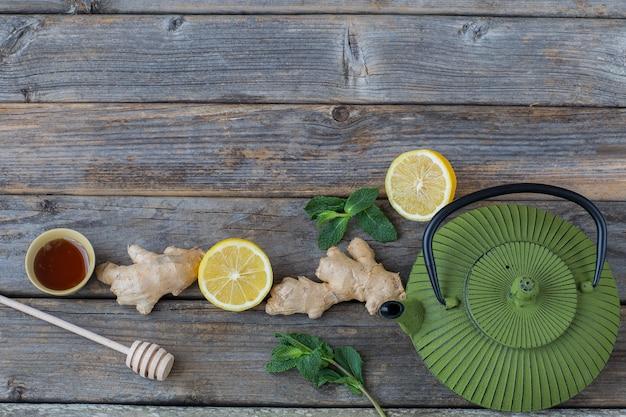 Czajnik, cytryna, miód, liście mięty i imbir na drewnianym stole - zdrowy styl życia