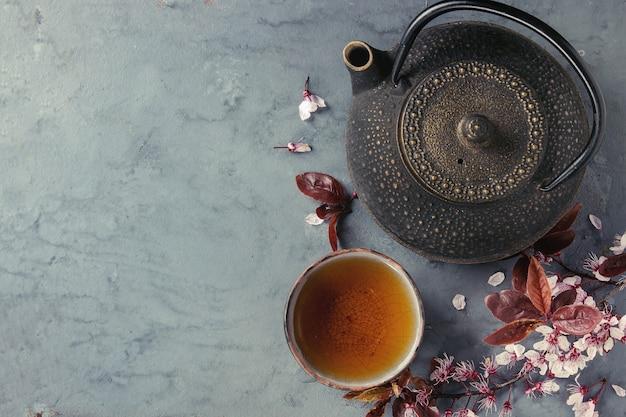 Czajnik i filiżanka herbaty z gałąź kwiat